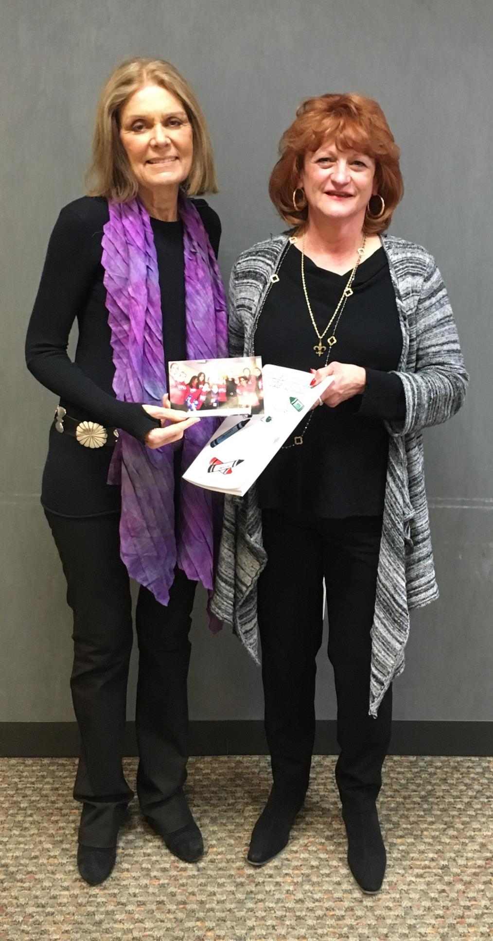 WILL program director Mary Lynn Hopps presents Steinem with a women's empowerment coloring book created by a WILL alum!
